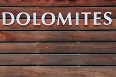 DOLOMITES text on wood background. DOLOMITES text on brown wood background Stock Photos