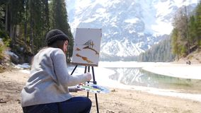 Dolomites. A young woman drawing on a canvas on an easel. Mid shot stock footage