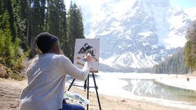 Dolomites. A young woman drawing mountains and forest on a canvas on an easel. Mid shot stock video footage