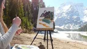 Dolomites. A young woman sitting on the coast of the river and drawing a painting of nature using easel. Mid shot stock video footage
