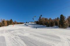 Dolomity, narciarski teren z pięknymi skłonami i niebieskie niebo, Pusty narciarski skłon w zimie na słonecznym dniu Przygotowywa fotografia royalty free