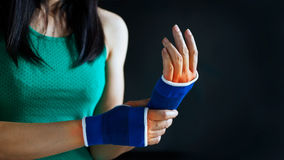 Dolor agudo en una muñeca de la mano de la mujer, seguridad en un vendaje del estiramiento, coloreado en rojo en fondo azul marin Imagen de archivo