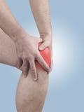 Dolor agudo en una rodilla del hombre. Mano que se sostiene masculina al punto de rodilla-ACH Foto de archivo