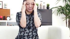 Dolor asiático de la sensación de la mujer en ojo con uso del teléfono móvil en casa metrajes