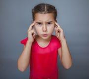 Dolor de cabeza adolescente de la jaqueca del niño de la muchacha en gris Foto de archivo libre de regalías