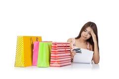 Dolor de cabeza asiático hermoso de la mujer con una declaración de la tarjeta de crédito y imagen de archivo libre de regalías