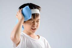 Dolor de cabeza del muchacho y paquete del gel del hielo foto de archivo