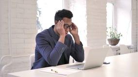 Dolor de cabeza, hombre de negocios subrayado Working en el ordenador portátil metrajes