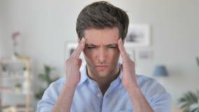 Dolor de cabeza, retrato del hombre joven hermoso tenso en oficina almacen de metraje de vídeo