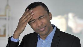 Dolor de cabeza, retrato del hombre de negocios afroamericano casual tenso en oficina almacen de video