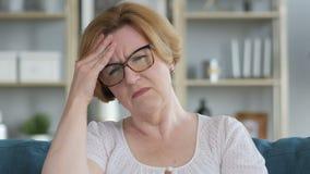 Dolor de cabeza, retrato de la vieja mujer mayor tensa en oficina metrajes