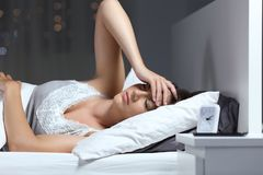 Dolor de cabeza sufridor de la mujer en la cama en casa en la noche Imágenes de archivo libres de regalías