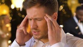 Dolor de cabeza sufridor masculino joven en el club, dando masajes a los templos y mirando alrededor almacen de video