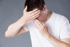 Dolor de cabeza y jaqueca, hombre con el dolor principal en fondo gris imagenes de archivo
