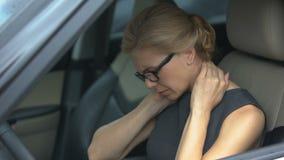 Dolor de cuello agotado de la sensación de la mujer, sentada en automóvil, problema espinal, salud metrajes