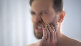 Dolor de diente masculino joven de la sensación, levantando la mano en mejilla, problemas dentales, cierre foto de archivo