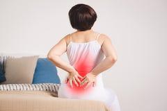 Dolor de espalda, inflamación del riñón, mujer que sufre de dolor de espalda en casa imagenes de archivo