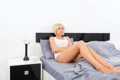 Dolor de estómago, mujer que miente en cama Imágenes de archivo libres de regalías