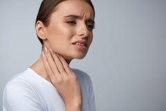 Dolor de la garganta Mujer hermosa que tiene garganta dolorida, sensación dolorosa foto de archivo