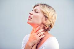 Dolor de la garganta Primer de la mujer enferma con la garganta dolorida que se siente mal, fotografía de archivo