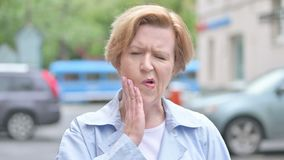 Dolor de muelas, mujer mayor al aire libre con dolor de diente almacen de metraje de vídeo