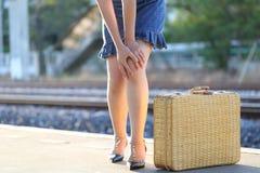 Dolor de sensaci?n de la mujer joven del primer en su rodilla en la estaci?n de tren, el concepto de la atenci?n sanitaria y de l fotos de archivo libres de regalías