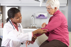 Dolor del codo del doctor Examining Female Patient With Fotografía de archivo libre de regalías