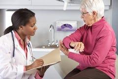 Dolor del codo del doctor Examining Female Patient With imagenes de archivo