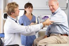 Dolor del codo del doctor Examining Male Patient With Imágenes de archivo libres de regalías