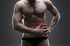 Dolor en el lado izquierdo Carrocería masculina muscular Culturista hermoso que presenta en fondo gris fotografía de archivo libre de regalías