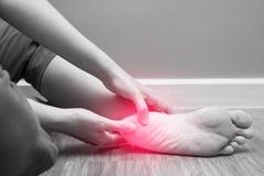 Dolor femenino del talón del pie con el punto rojo, fasciitis plantar Imágenes de archivo libres de regalías