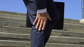 Dolor masculino de la rodilla de la sensación del hombre de negocios, caminando abajo, lesión común, primer almacen de metraje de vídeo