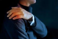 Dolor pesado del hombro de la mujer de negocios coloreado en rojo en fondo azul marino fotografía de archivo