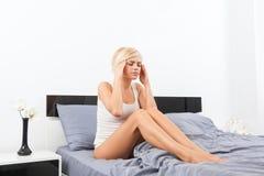 Dolor principal de la mujer trastornada que se sienta en cama Imagen de archivo