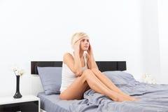 Dolor principal de la mujer trastornada que se sienta en cama Fotografía de archivo