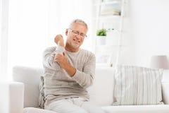 Dolor sufridor infeliz del codo del hombre mayor en casa Imagen de archivo libre de regalías