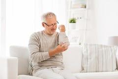 Dolor sufridor infeliz del codo del hombre mayor en casa Foto de archivo