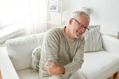 Dolor sufridor infeliz del codo del hombre mayor en casa Fotografía de archivo
