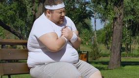 Dolore acuto ritenente dell'uomo grasso nel cuore, rischio di infarto, conseguenze di obesità archivi video