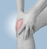 Dolore acuto in un ginocchio dell'uomo. Mano maschio della tenuta al punto di ginocchio-ACH Immagini Stock