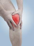Dolore acuto in un ginocchio dell'uomo. Mano maschio della tenuta al punto di ginocchio-ACH Fotografia Stock