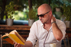 Dolore al collo del giovane mentre leggendo un libro Immagine Stock