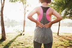dolore alla schiena del corridore femminile dopo avere corso al parco Fotografia Stock