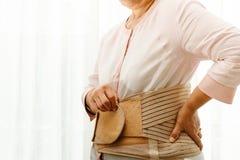 Dolore alla schiena, donna senior che indossa indietro la cinghia di sostegno su fondo bianco fotografia stock libera da diritti