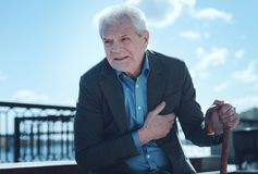 Dolore anziano esaurito di sensibilità dell'uomo nell'area del cuore fotografia stock