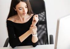 Dolore del braccio L'impiegato di concetto femminile sta avendo lesione di sindrome dell'ufficio sul suo polso immagini stock
