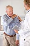 Dolore del dottore Examining Patient With Shoulder Fotografia Stock Libera da Diritti