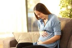 Dolore di pancia di sofferenza della donna incinta fotografia stock