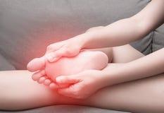 Dolore femminile con il punto rosso, sindrome del tallone del piede di Sesamoiditis fotografia stock