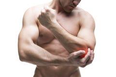 Dolore nel gomito Ente maschio muscolare Culturista bello che posa nello studio Isolato su fondo bianco con il punto rosso Fotografia Stock